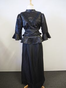 Black Victorian ladies costume, includes a high necked blouse and bustled skirt