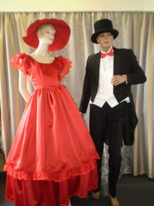1800's men's tailed suit and woman's red hooped crinoline dress